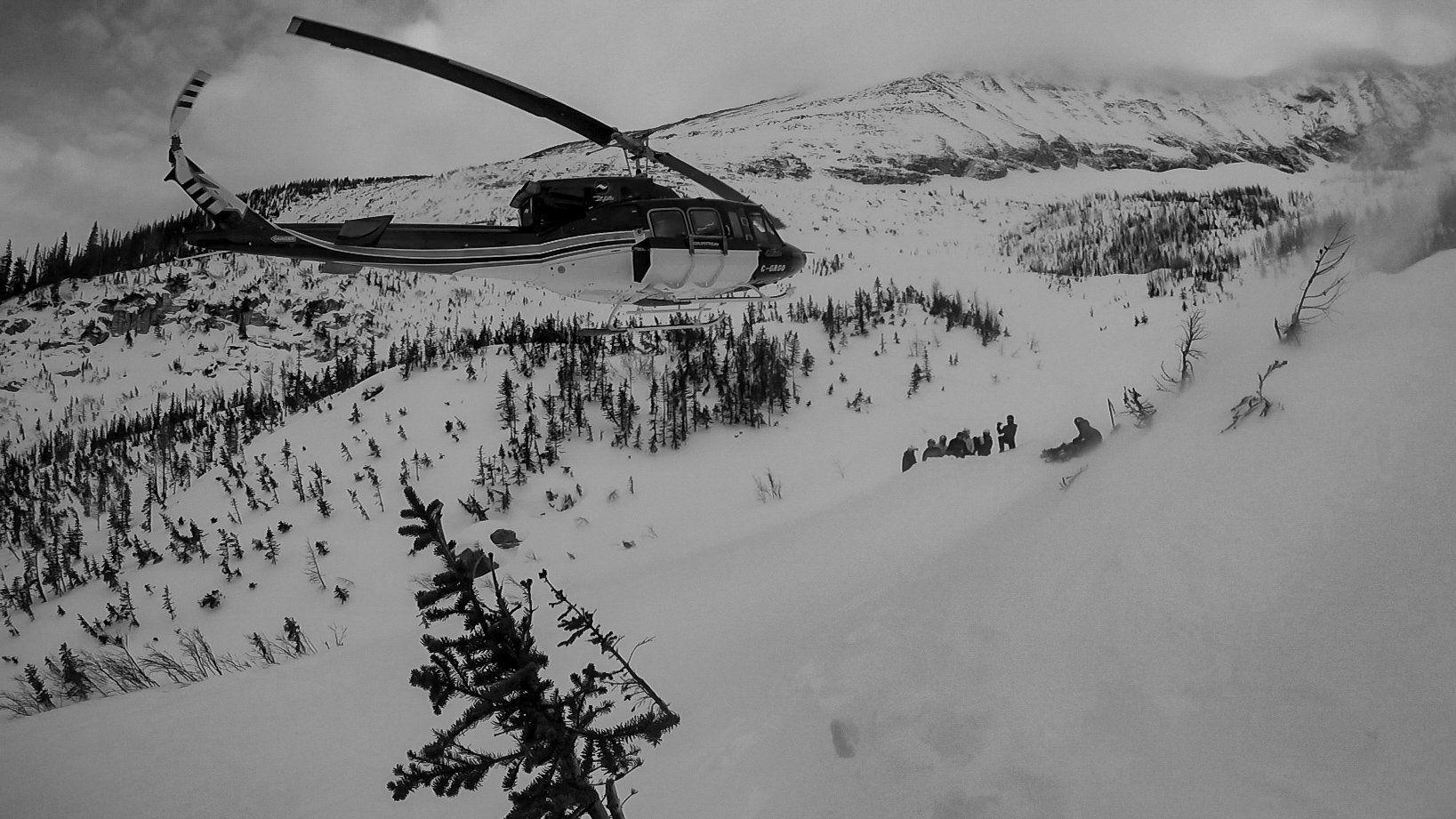 Hélicoptère prêt à récupérer un group de skieurs