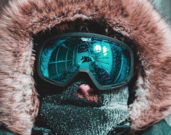 un skieur avec un masque de ski et une capuche à poil.